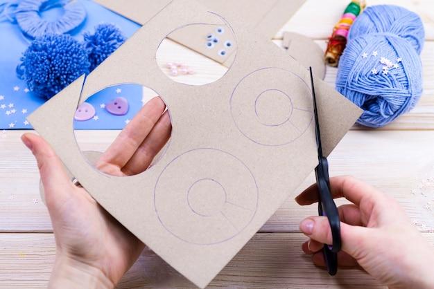 Zestaw do robótek ręcznych na drewnianym stole. nici, nożyczki, papier do robienia pomponów.