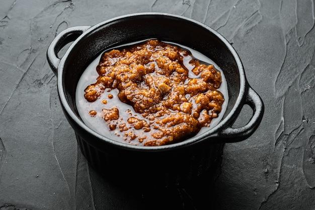 Zestaw do sosu włoskiego z czerwonym pesto, w misce, na czarnym kamiennym tle