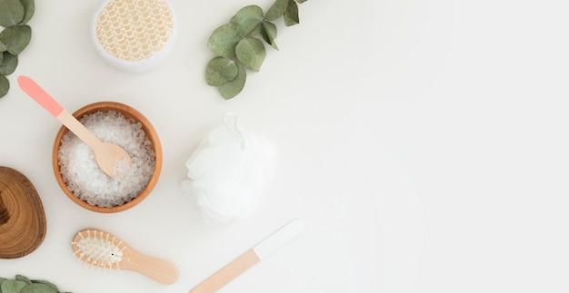 Zestaw do spa piękności z solą, eukaliptusem i drewnianymi akcesoriami na białym tle