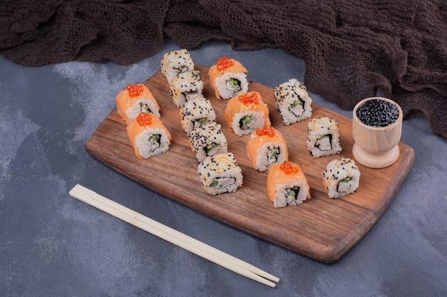 Zestaw do sushi. filadelfia i alaska toczą się na drewnianym talerzu z pałeczkami.