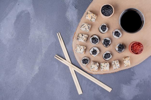 Zestaw do sushi. roladki sushi z maki i alaski na drewnianym talerzu z pałeczkami, kawiorem i sosem sojowym.