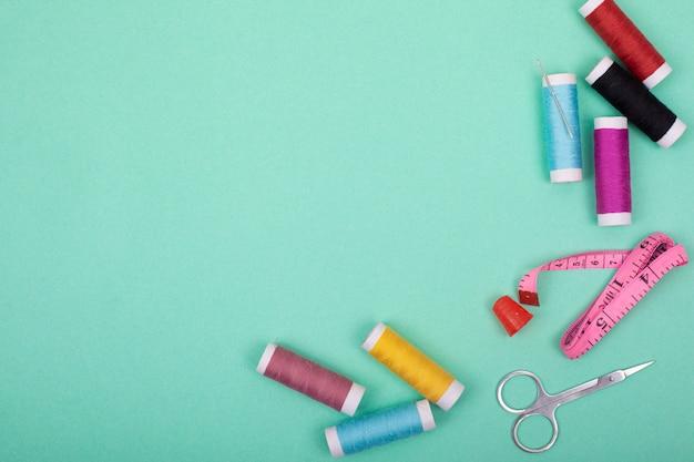 Zestaw do szycia akcesoria. zestaw narzędzi do szycia i kolorowe nici, igły, szpilki, nożyczki na miętowym tle makieta rama widok z góry.