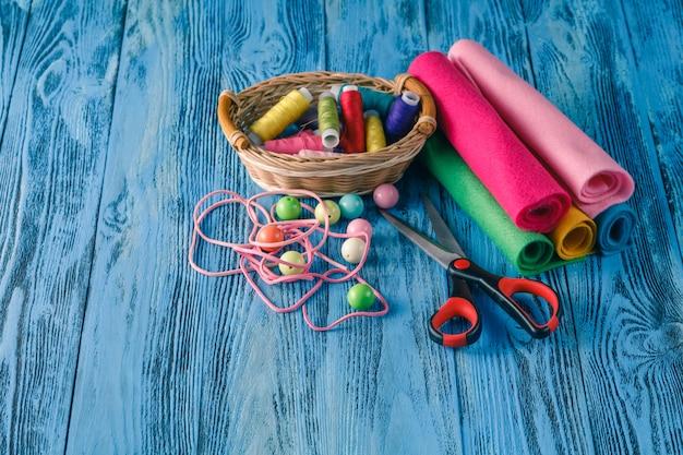 Zestaw do szycia na drewnianym stole. nici, igły, nożyczki i zabawka na stole.