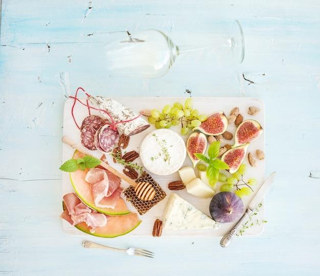 Zestaw do wina i przekąsek. figi, winogrona, orzechy, odmiana sera, przekąski mięsne, zioła, szkło na jasnoniebieskim, widok z góry.
