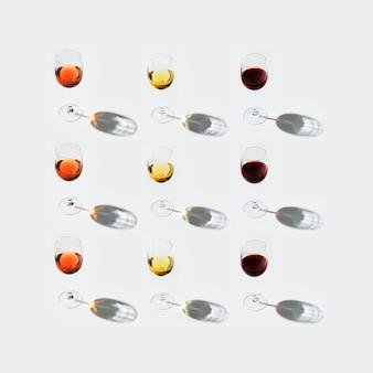 Zestaw do wina w kieliszkach. czerwone, różowe i białe wino na jasnym tle. kartka z życzeniami. koncepcja bar, winiarnia, degustacja.