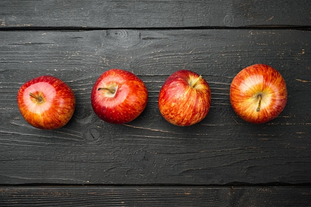 Zestaw dojrzałych czerwonych jabłek, na tle czarnego drewnianego stołu, płaski widok z góry, z miejscem na kopię tekstu