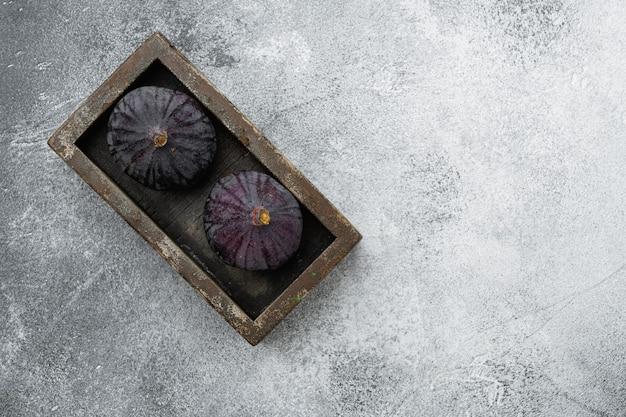 Zestaw dojrzałych fig, na szarym tle kamiennego stołu, płaski widok z góry, z miejscem na kopię tekstu