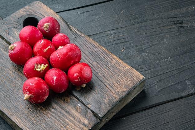 Zestaw dojrzałych rzodkiewek, na drewnianej desce do krojenia, na tle czarnego drewnianego stołu, z copyspace i miejsca na tekst
