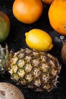 Zestaw dojrzałych soczystych świeżych owoców tropikalnych, na tle czarnego ciemnego kamiennego stołu, widok z góry płaski lay