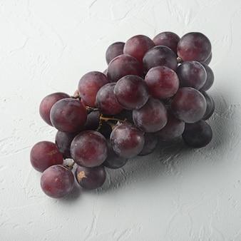 Zestaw dojrzałych winogron, ciemnoczerwone owoce, kwadratowy format, na białym kamiennym stole
