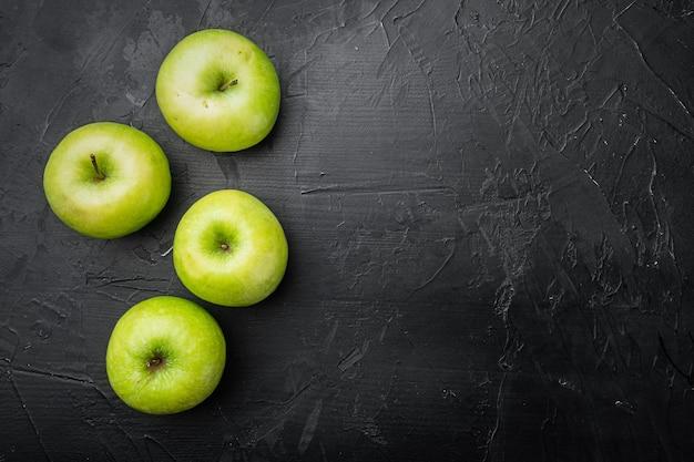 Zestaw dojrzałych zielonych jabłek, na tle czarnego ciemnego kamiennego stołu, płaski widok z góry, z miejscem na kopię tekstu