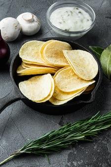 Zestaw domowych chipsów ziemniaczanych, na szarym tle kamienia