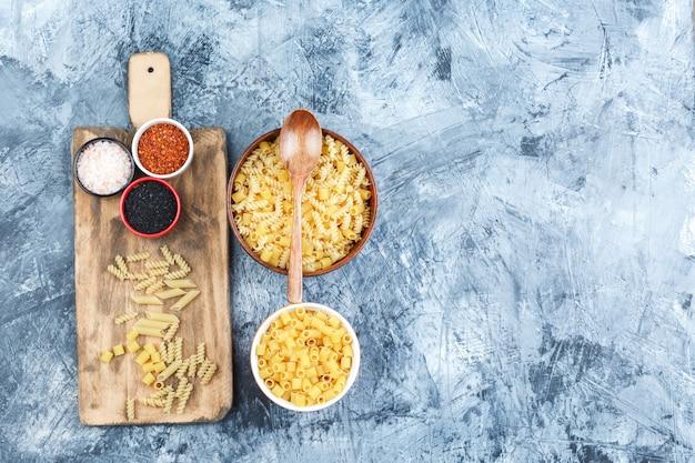 Zestaw drewnianą łyżką, przyprawami i surowym makaronem w miseczkach na szarym tynku i tło deska do krojenia. widok z góry.