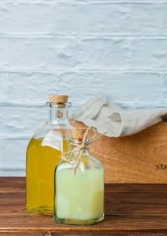 Zestaw drewnianej skrzyni i białej szmatki i butelki soku z cytryny na drewnianej i białej powierzchni. widok z boku. miejsce na tekst