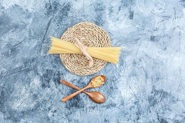 Zestaw drewnianych łyżek i spaghetti na tle szarego tynku i wiklinowej podkładki. widok z góry.