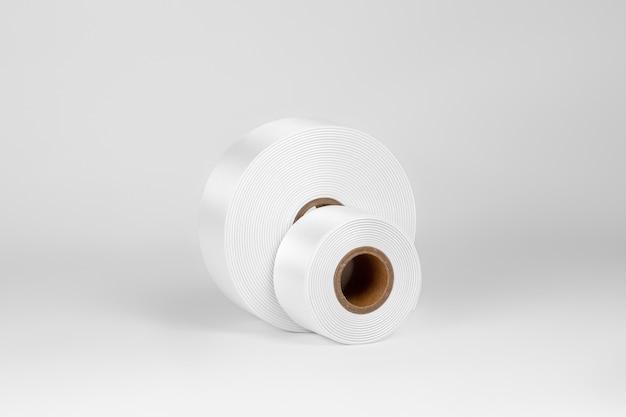 Zestaw dwóch cewek szerokich białych satynowych wstążek na metki lub wystrój na białym tle