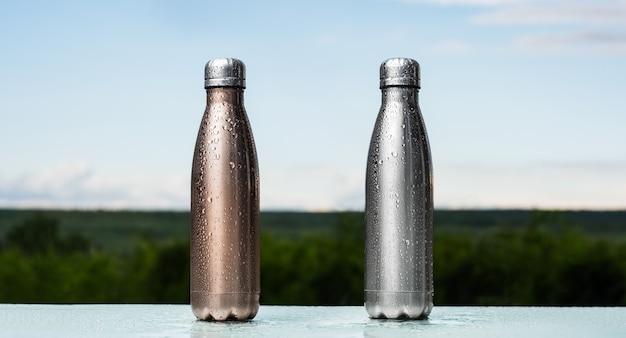 Zestaw eko termosów wielokrotnego użytku z korkiem, spryskanych wodą. kolor brązowy i srebrny. zbliżenie