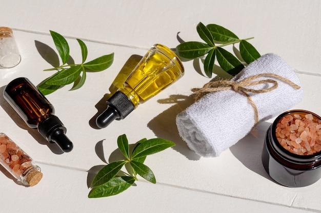 Zestaw ekologicznych niemarkowych kosmetyków do pielęgnacji twarzy. zabiegi kosmetyczne na biały drewniany stół z zielonymi liśćmi. ekologiczne akcesoria spa.