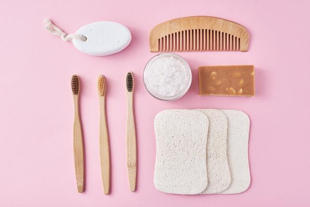 Zestaw ekologicznych przedmiotów higieny osobistej na różowej powierzchni. bambusowa szczoteczka do zębów, drewniany grzebień, gąbka, mydło i sól morska, widok z góry leżał płasko. koncepcja zero odpadów