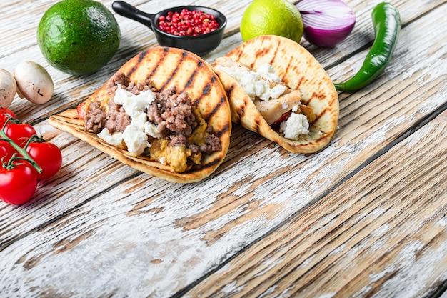 Zestaw exican taco z wołowiną i mięsem z kurczaka i składników, na tle białej powierzchni drewnianej teksturowanej, widok z boku, miejsce na tekst.