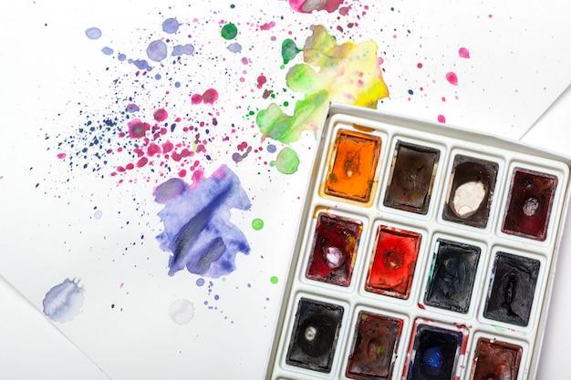 Zestaw farb akwarelowych z próbkami rozpryski farby na papierze