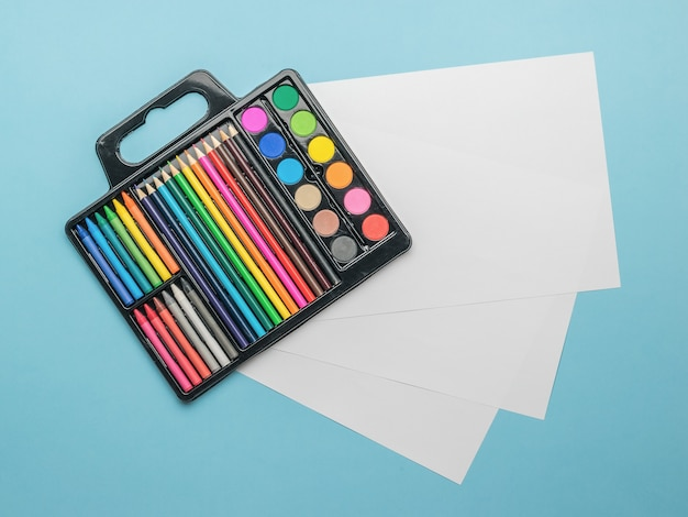 Zestaw farb, ołówków i kredek oraz puste kartki papieru na niebieskim tle. akcesoria dla kreatywności.