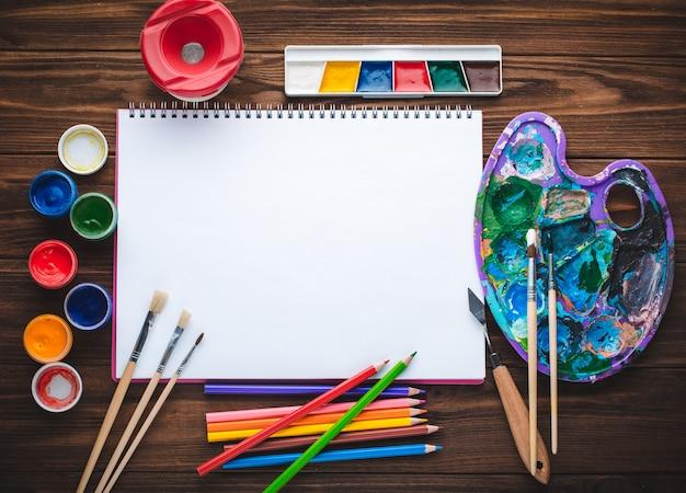 Zestaw farb, ołówków, narzędzi do malowania i pusty arkusz białego papieru