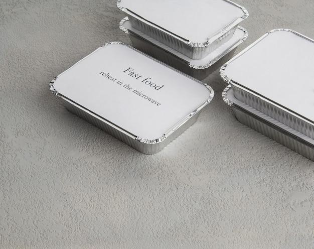 Zestaw fast foodów w pudełku z folii na szarym szorstkim tle. jedzenie dla biznesmenów i ludzi zapracowanych