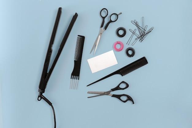 Zestaw fryzjerski z różnymi akcesoriami na niebieskim tle