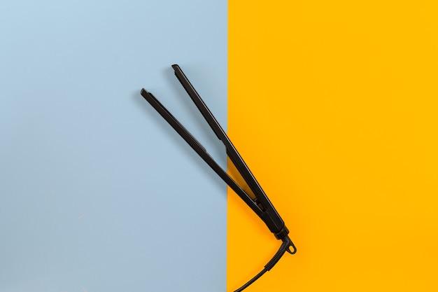 Zestaw fryzjerski z różnymi akcesoriami na pomarańczowym i niebieskim tle. widok z góry. skopiuj miejsce. martwa natura. makieta. płaskie ułożenie