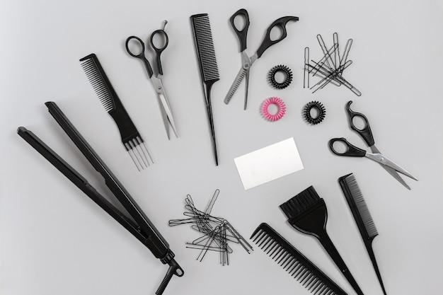Zestaw fryzjerski z różnymi akcesoriami na szarym tle