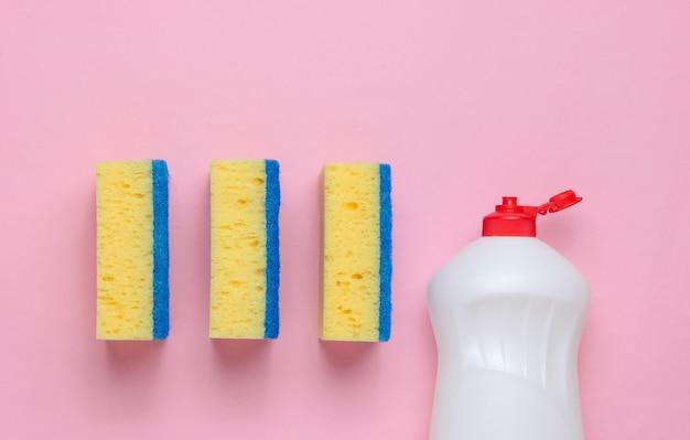 Zestaw gospodyń domowych do mycia naczyń. zmywarka. butelka do mycia naczyń, gąbki na różowym tle. widok z góry.