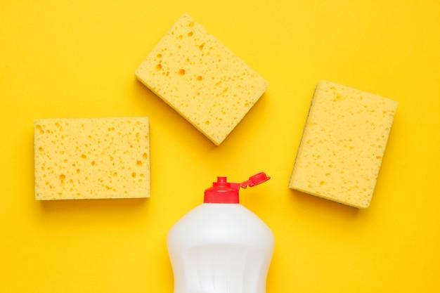Zestaw gospodyń domowych do mycia naczyń. zmywarka. butelka naczyń do mycia, gąbki na żółtym tle. widok z góry.