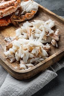 Zestaw gotowanych niebieskich części kraba pływackiego, na szarym tle