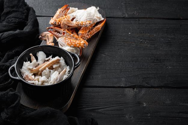 Zestaw gotowanych niebieskich pazurów kraba na czarnym drewnianym stole