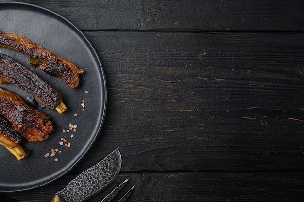 Zestaw grillowanych żeber wieprzowych, na talerzu, na czarnym drewnianym stole, widok z góry na płasko