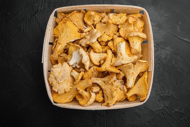Zestaw grzybów kurkowych, w drewnianym pudełku, na czarnym ciemnym tle kamiennego stołu, widok z góry płaska lay