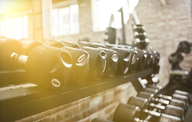 Zestaw hantli w kolorze czarnym z metalowymi uchwytami na stojaku na siłowni. trening z wolnymi ciężarami, kulturystyka
