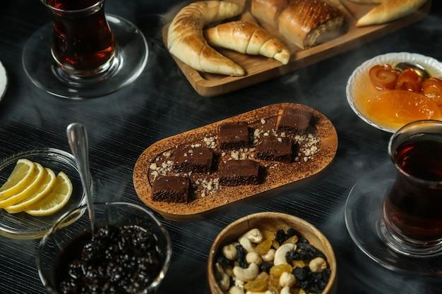 Zestaw herbaciany z suszonymi owocami, cytryną, orzechami, dżemem i ciastami