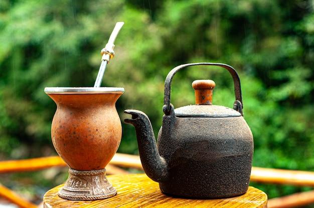 Zestaw herbaty z czajnikiem na rustykalnym drewnianym stołku