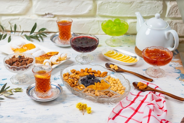 Zestaw herbaty z odmianami tradycyjnych orzechów, cytryny, konfitury i słodyczy serwowanych na białym obrusie