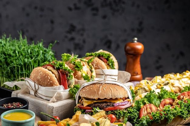 Zestaw hot dogi, hamburgery i frytki na drewnianym stole. przekąski typu fast food. koncepcja fast foodów i fast foodów