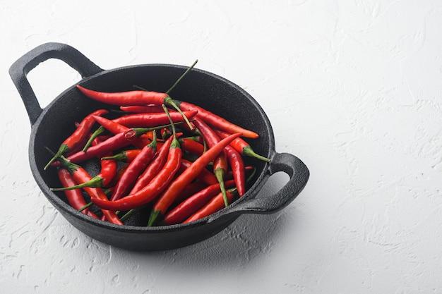 Zestaw hot red do papryki tajskiej na żeliwnej patelni, na stole z białego kamienia