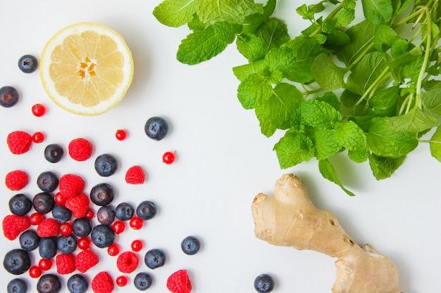 Zestaw jagód, czerwonych porzeczek, cytryny, imbiru, liści mięty i malin na białej powierzchni. widok z góry.
