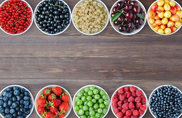 Zestaw jagód na okrągłych talerzach. brązowe drewniane tła. skopiuj miejsce.