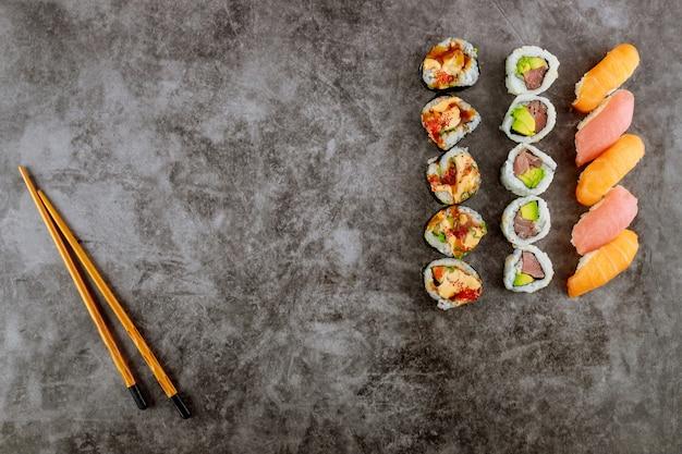 Zestaw japońskiej rolki sushi z pałeczką na szarym tle. owoce morza.