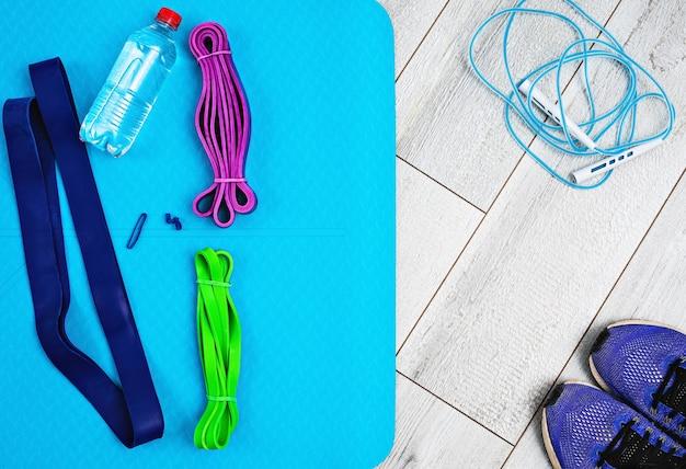 Zestaw jasnych gumek lateksowych na fitness, matę do jogi i butelkę wody