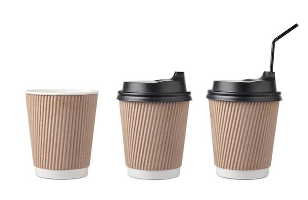 Zestaw jednorazowych kubków papierowych do kawy z czarnymi czapkami na białym tle.