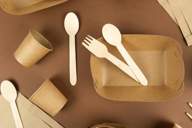 Zestaw jednorazowych zastaw stołowych i drewnianych sztućców na brązowym tle pojemniki na fast food