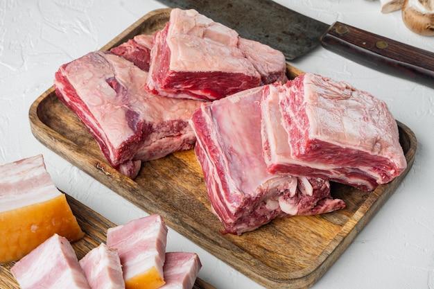 Zestaw kalbi surowych żeber wołowych, ze składnikami i starym nożem rzeźniczym, na białym kamiennym tle